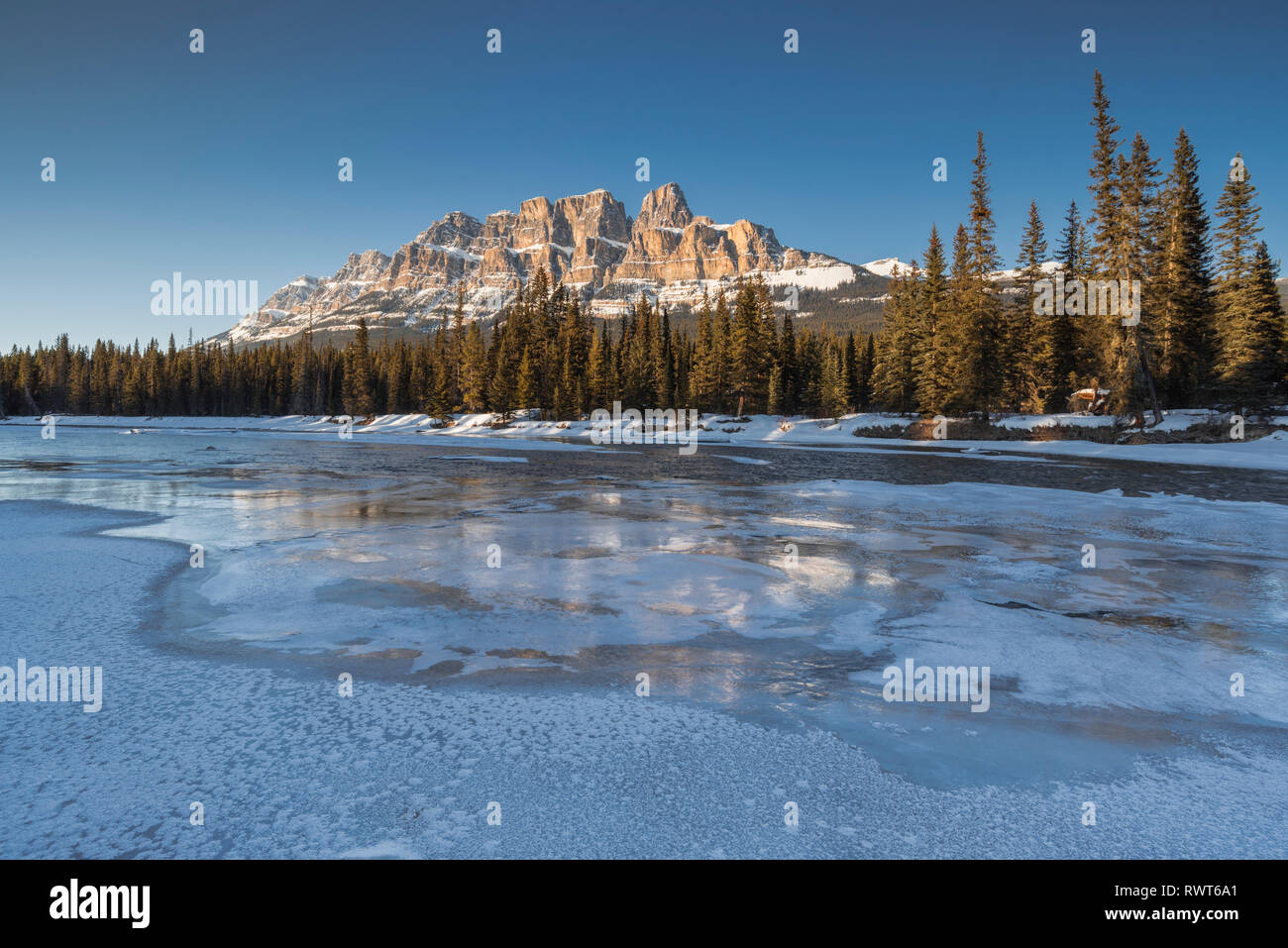 Castle Mountain in winter at sunset with frozen Bow River, Banff National Park, Canada, Canadian Rockies - Stock Image