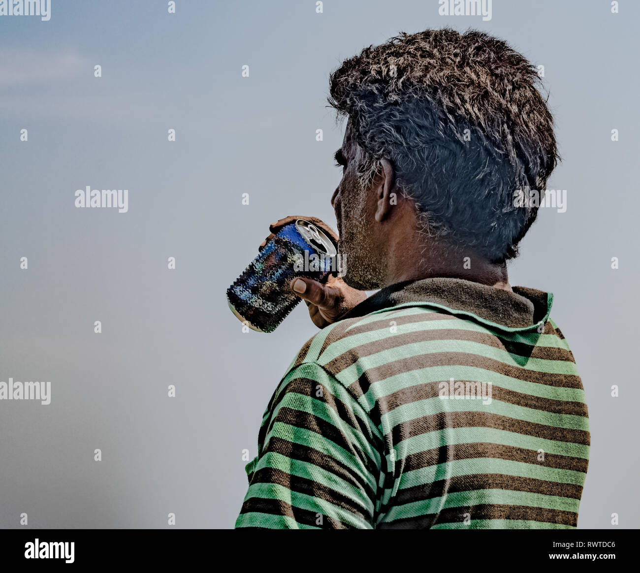 Middle Aged Fisherman of South Asian Origin, wearing striped tshirt is exhausted and quenching his thirst by drinking beer/cold drink on hot sunny day - Stock Image