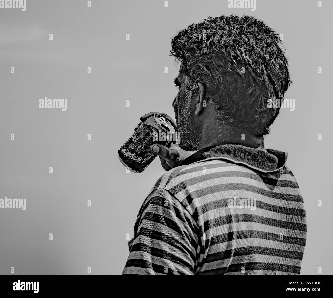 Black & White photo of middle aged man wearing striped tShirt and quenching thirst by drinking beer/cold drink from an aluminum can on hot sunny day - Stock Image
