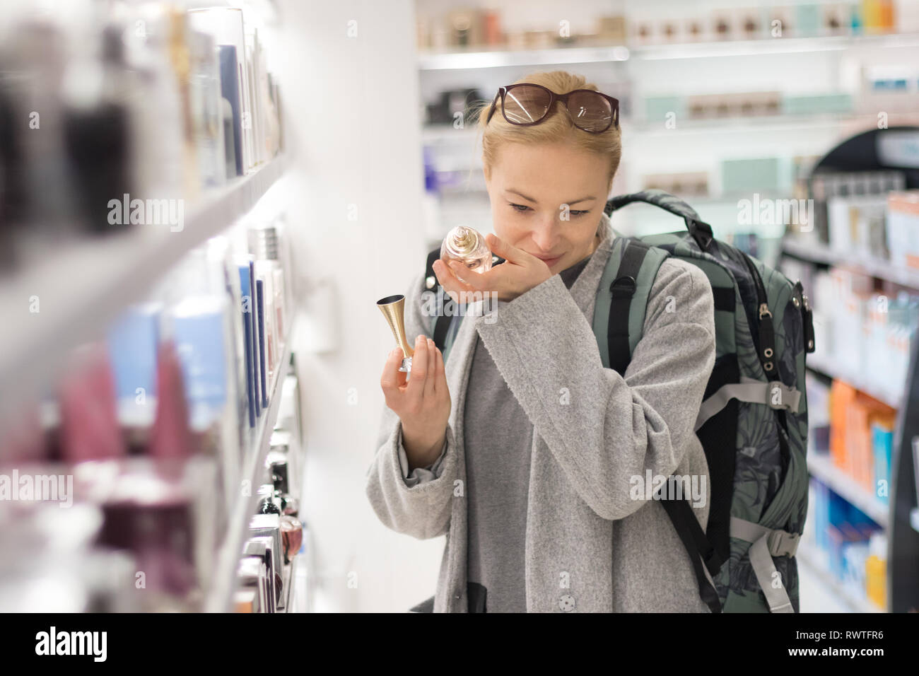 0d027205c6f0 Blond young female traveler wearing travel backpack choosing perfume in airport  duty free store. -