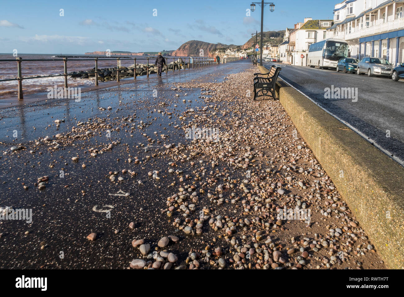Pebble and shale from the beach thrown onto the seafront Esplanade at Sidmouth by a storm. - Stock Image