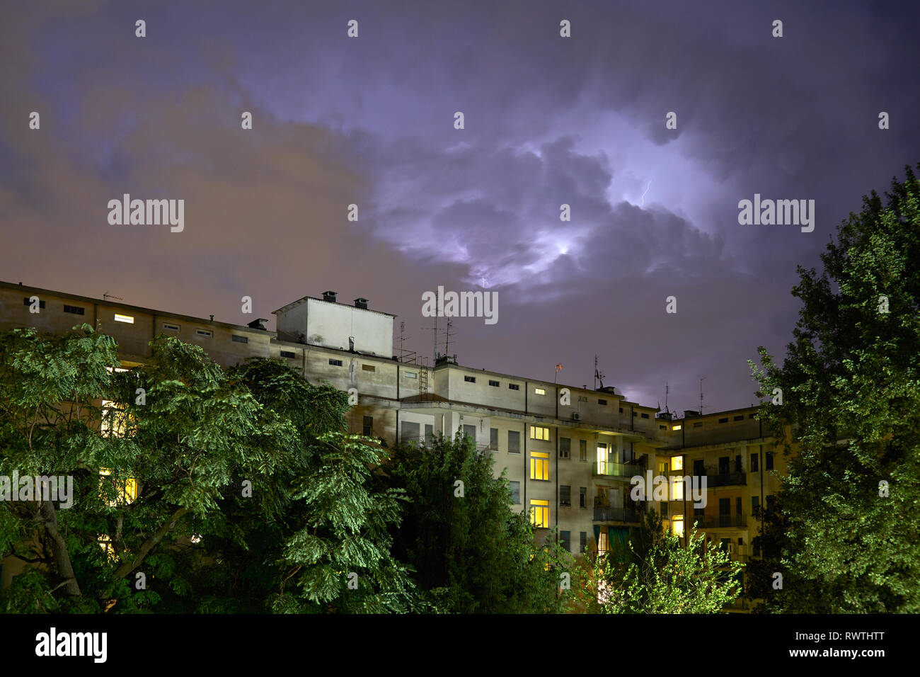 Buildings and green trees at night, illuminated sky during a lightning storm in Italy Stock Photo