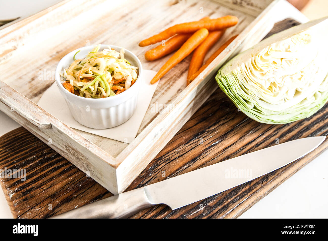 Side view of bowl filled with coleslaw isolated on wood background Stock Photo