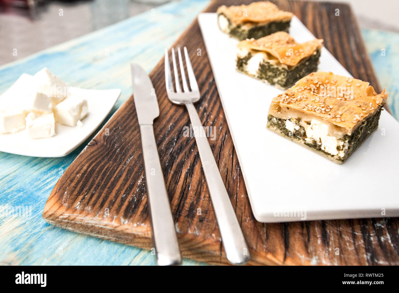 Strudel with spinach and ricotta on a dark wood background. Stock Photo