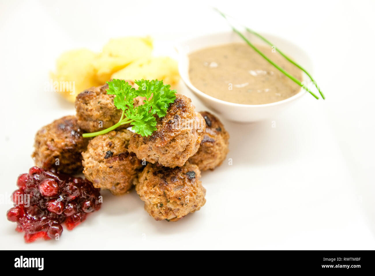 Meatballs stewed with vegetables on white background Stock Photo