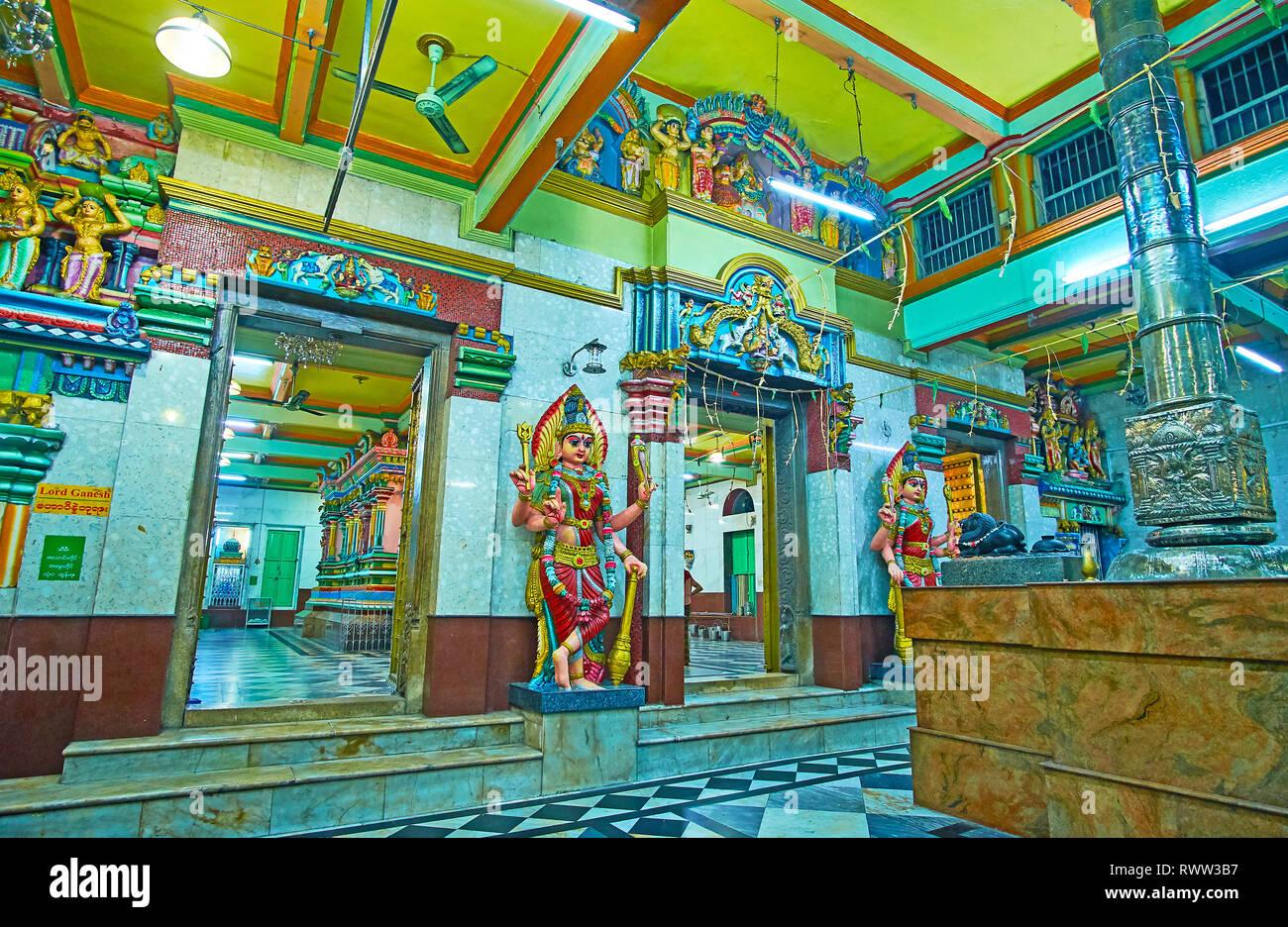 YANGON, MYANMAR - FEBRUARY 15, 2018: Interior of Mandapa hall of Sri Kaali Amman Hindu Temple, decorated with colorful statues of Hindu deities, on Fe - Stock Image