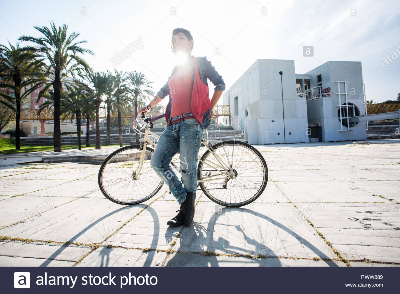 Young woman with bicycle in the streets - Stock Image