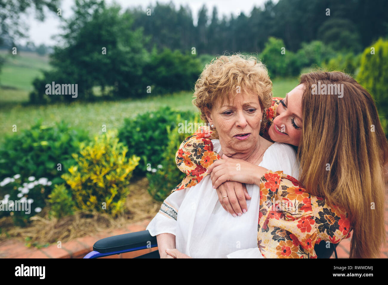 Senior dissatisfied woman in a wheelchair with her daughter - Stock Image