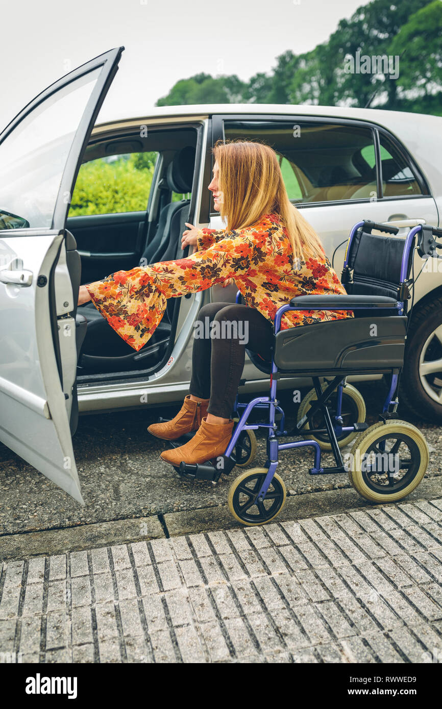 Woman in wheelchair getting on car - Stock Image