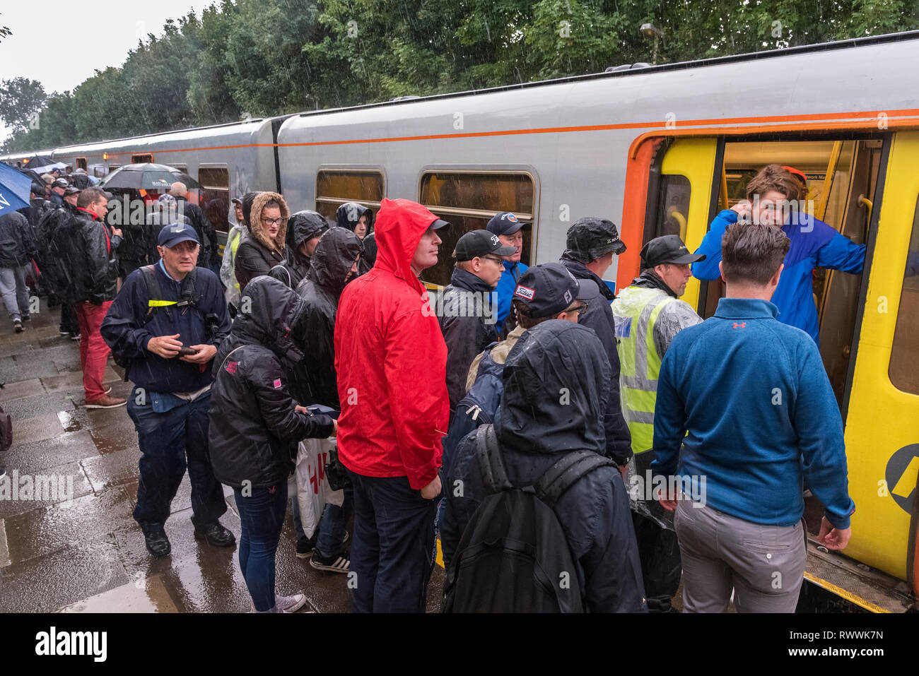Merseyrail train passengers in pouring rain . - Stock Image