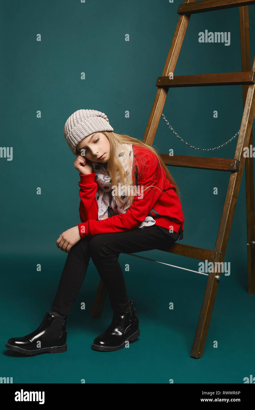 Pensive teenage girl, beautiful young model girl with long blonde hair in black jeans and in fashionable red sweatshirt sitting on a step ladder at - Stock Image