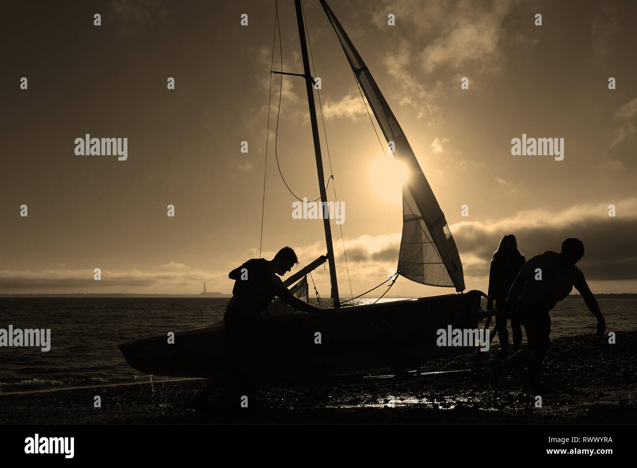 Monochrome silhouette of dinghy boat recovery approaching sunset. A magical scene. Stock Photo