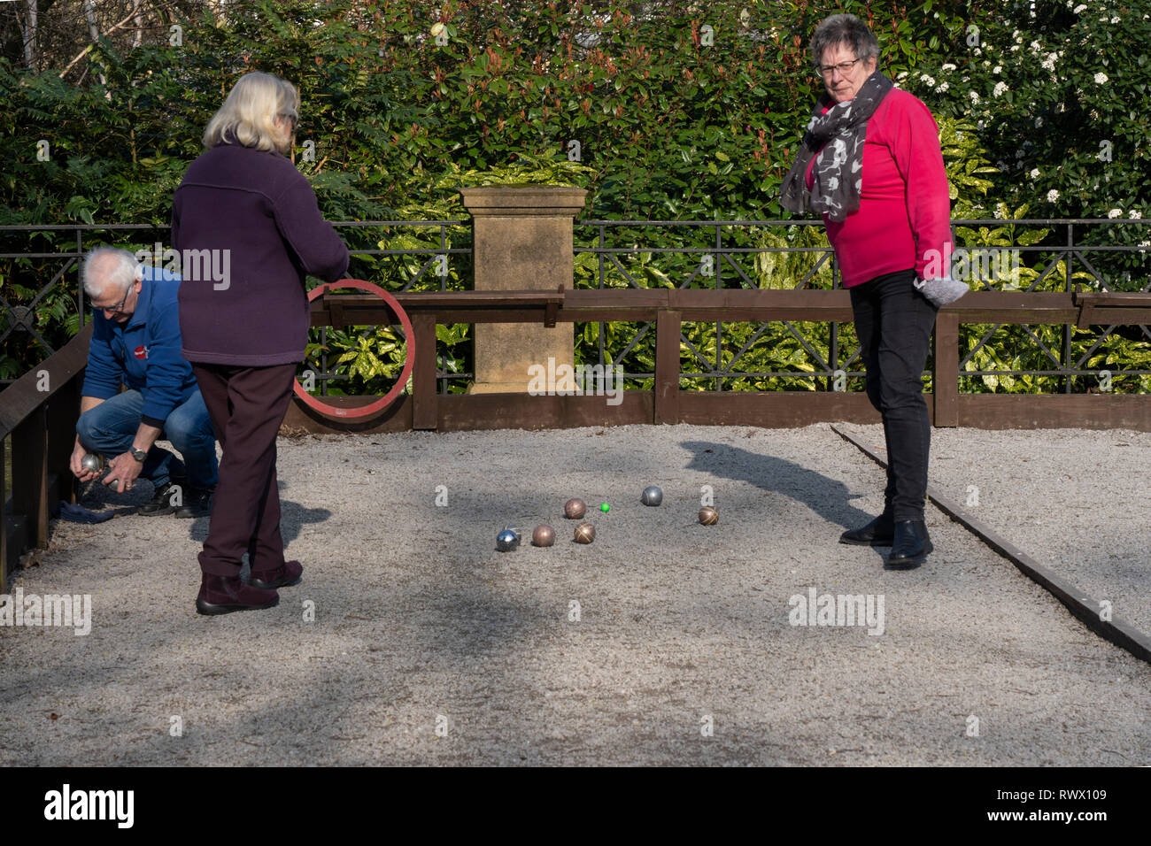 Three people playing a game of Petanque outdoors in Harrogate,North Yorkshire,England,UK. - Stock Image
