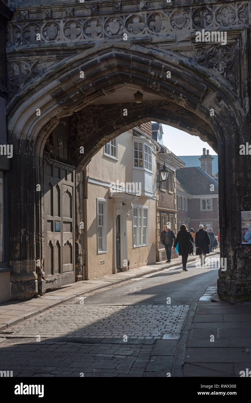 Salisbury, Wiltshire, England, UK. March 2019. Visitors passing through the North Gate of the city towards Cathedral Close from the High Street Stock Photo