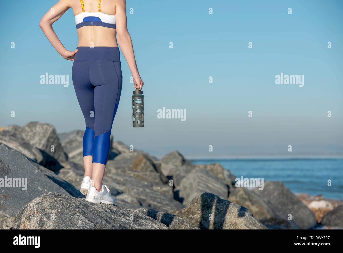 close up of a sports water bottle, womans legs in sportswear leggings - Stock Image