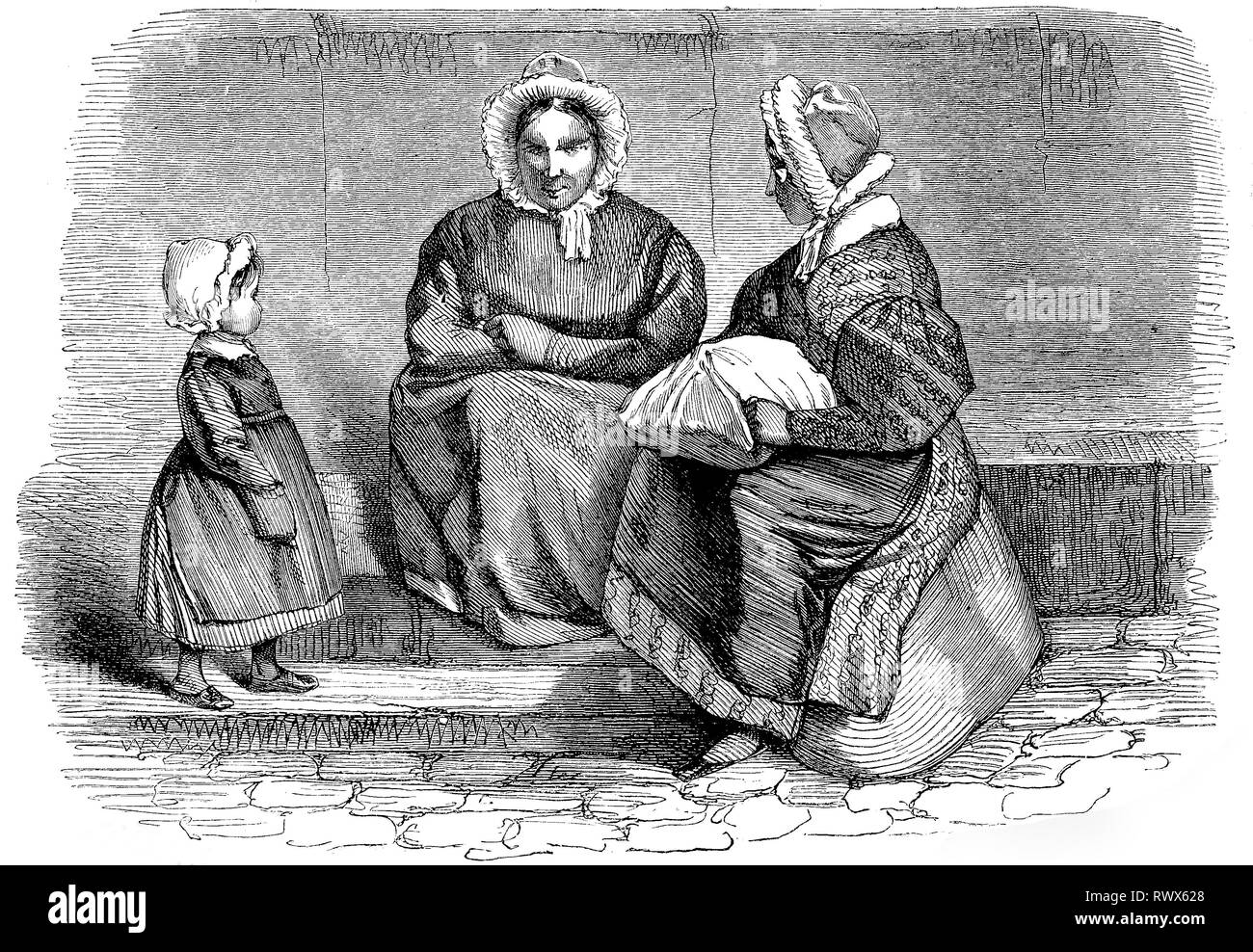 Zwei Frauen und ein Kind sitzen an der Straße / two women and a child sitting in the street - Stock Image