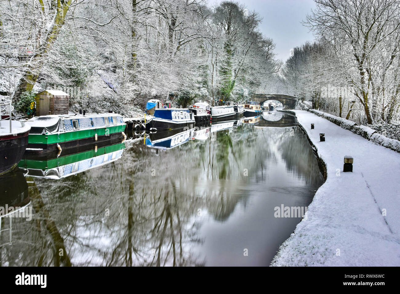 Narrowboats reflected on the frozen wintry snowy Rochdale Canal and towpath, Hebden Bridge, Calderdale, West Yorkshire - Stock Image