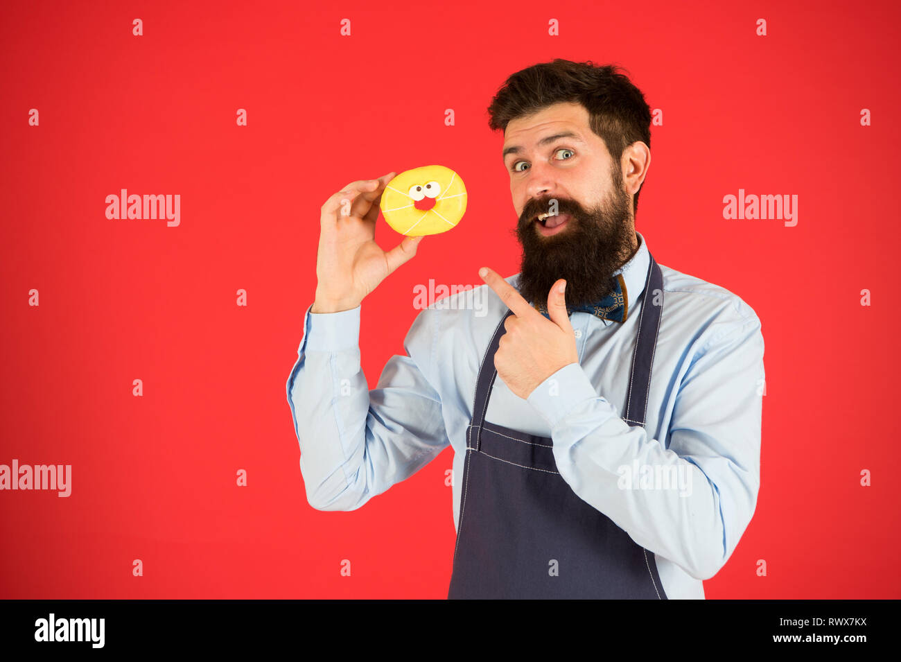 Cheat meal. Hipster bearded baker hold glazed donut on red background. Cafe and bakery concept. Sweet donut from baker. Man bearded baker in cooking apron hold cute dessert. Forget about diet. - Stock Image