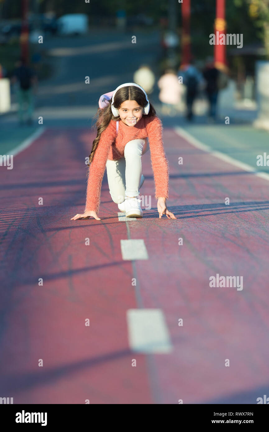 I am ready ready to start mp3 player happy little girl audio book kid in headphones little girl standing on start line while running outdoor little