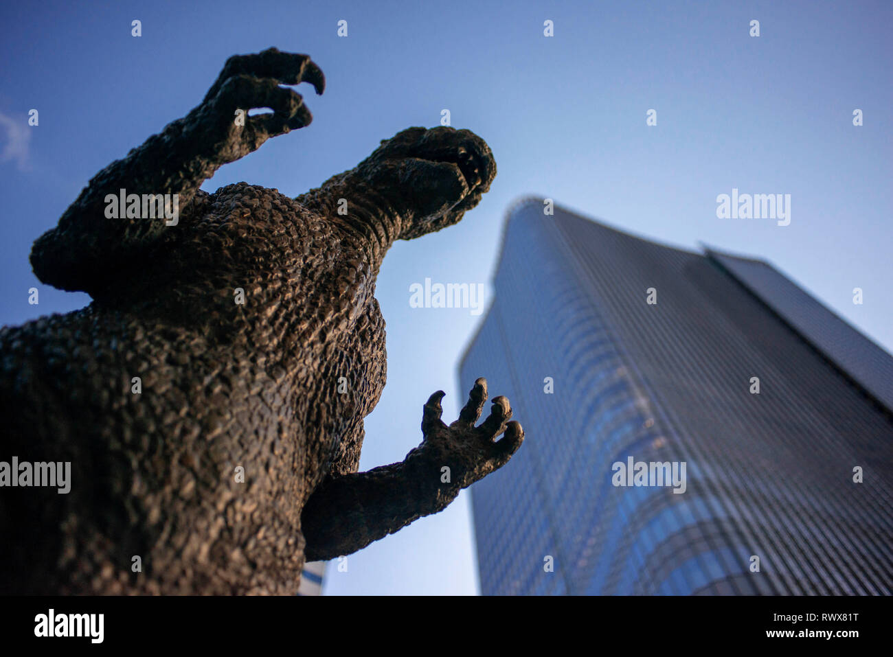 Bronze statue of Godzilla, creature movie star from 1950's, sits on a prominent pedestal in Hibiya cinema district in Tokyo. - Stock Image