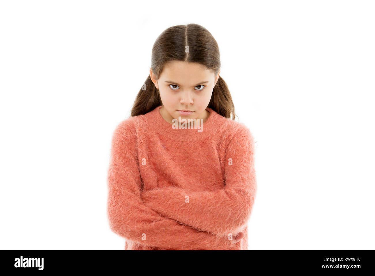 Still angry. Disagreement and stubbornness. Girl serious face offended white background. Kid little girl unhappy looks strictly. Girl folded arms on chest looks serious. Stubborn child temper. - Stock Image