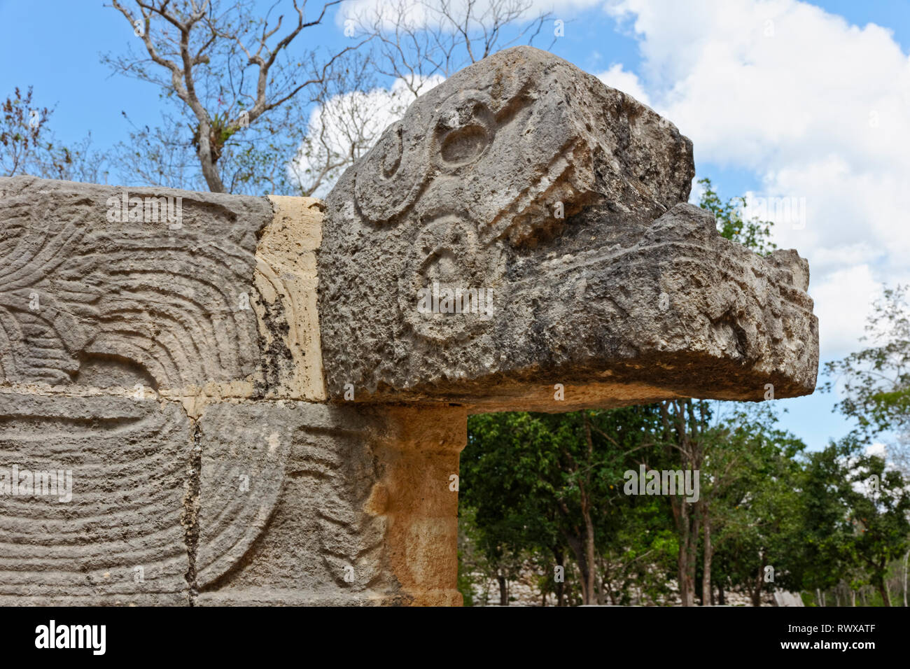 Close up of the head of a mayan carved stone snake with geometric patterns on the body from Chechen Itza - Stock Image