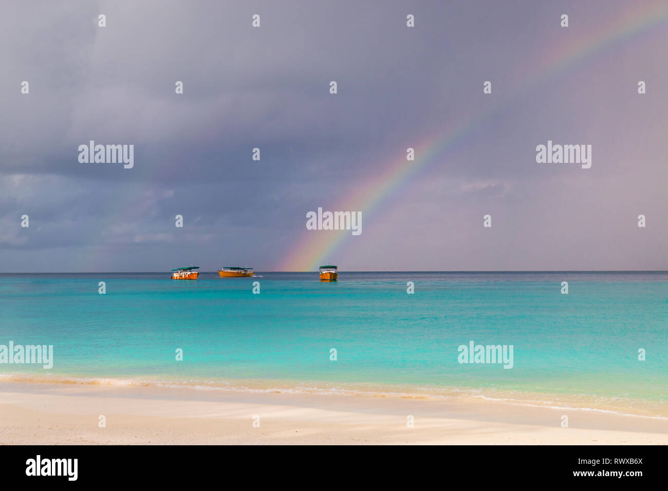 Rainbow in Paradise - beautiful rainbow on the maledives with boats in the the background - Stock Image