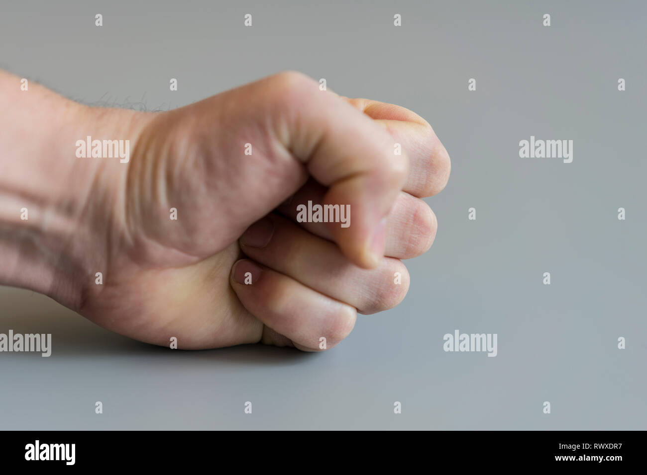 fist on gray background. The concept of domestic violence. Male rudeness and violence. - Stock Image