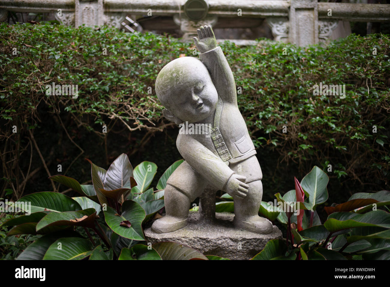 Fo Guang Shan - Largest Buddhist Monastery in Taiwan-A cute small stone buddha statue in the gardens of the temple in exercise pose. Kaohsiung, 2018 - Stock Image
