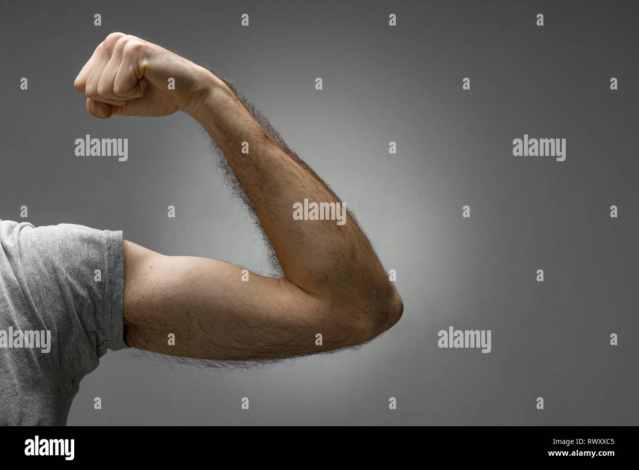 Close-Up of a Thin Hairy Arm Contracting the Biceps - Stock Image
