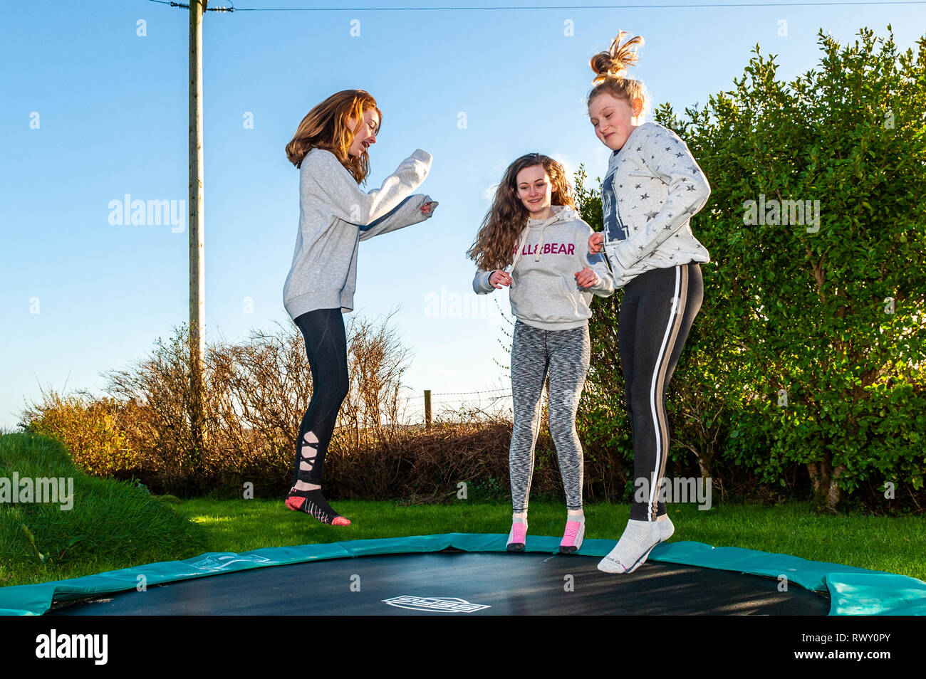 Ballydehob, West Cork, Ireland. 7th March, 2019. Girls make the most of the hot, sunny weather by bouncing on a trampoline. The day will continue to be sunny whilst tomorrow will start off dry with showers developing in the afternoon. Credit: Andy Gibson/Alamy Live News. - Stock Image