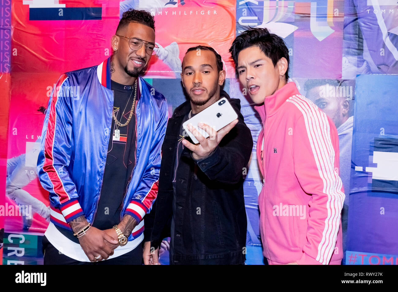 Berlin, Germany. 07th Mar, 2019. Jerome Boateng (l-r), soccer player, Lewis Hamilton, racing driver, and Jacky Heung, actor, stand in front of a photo wall at the Tommy Hilfiger CREATExUNITY event and make a selfie. Credit: Christoph Soeder/dpa/Alamy Live News - Stock Image