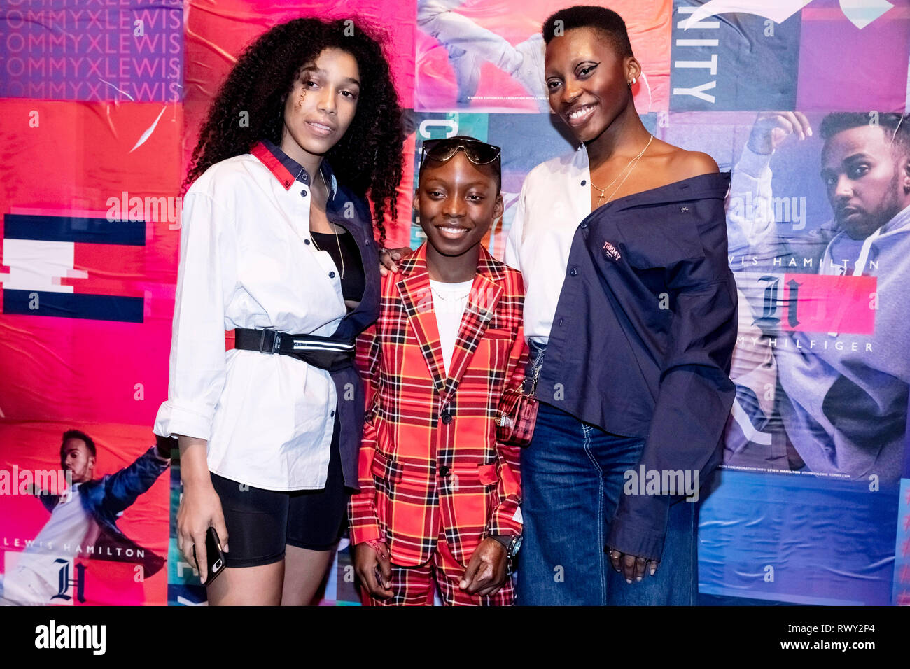 07 March 2019, Berlin: Toni Dreher-Adenuga (r), model, stands with her brother (M) and another person at the Tommy Hilfiger CREATExUNITY event in front of a photo wall. Photo: Christoph Soeder/dpa - Stock Image