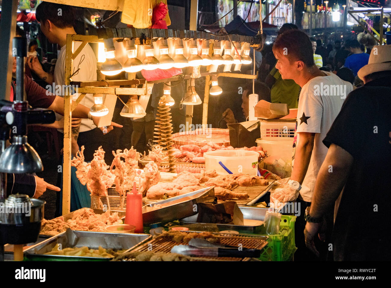 fried and BBQ meat seller and customer  stall at Jalan Alor food street and night market in Kuala Lumpur Malaysia - Stock Image