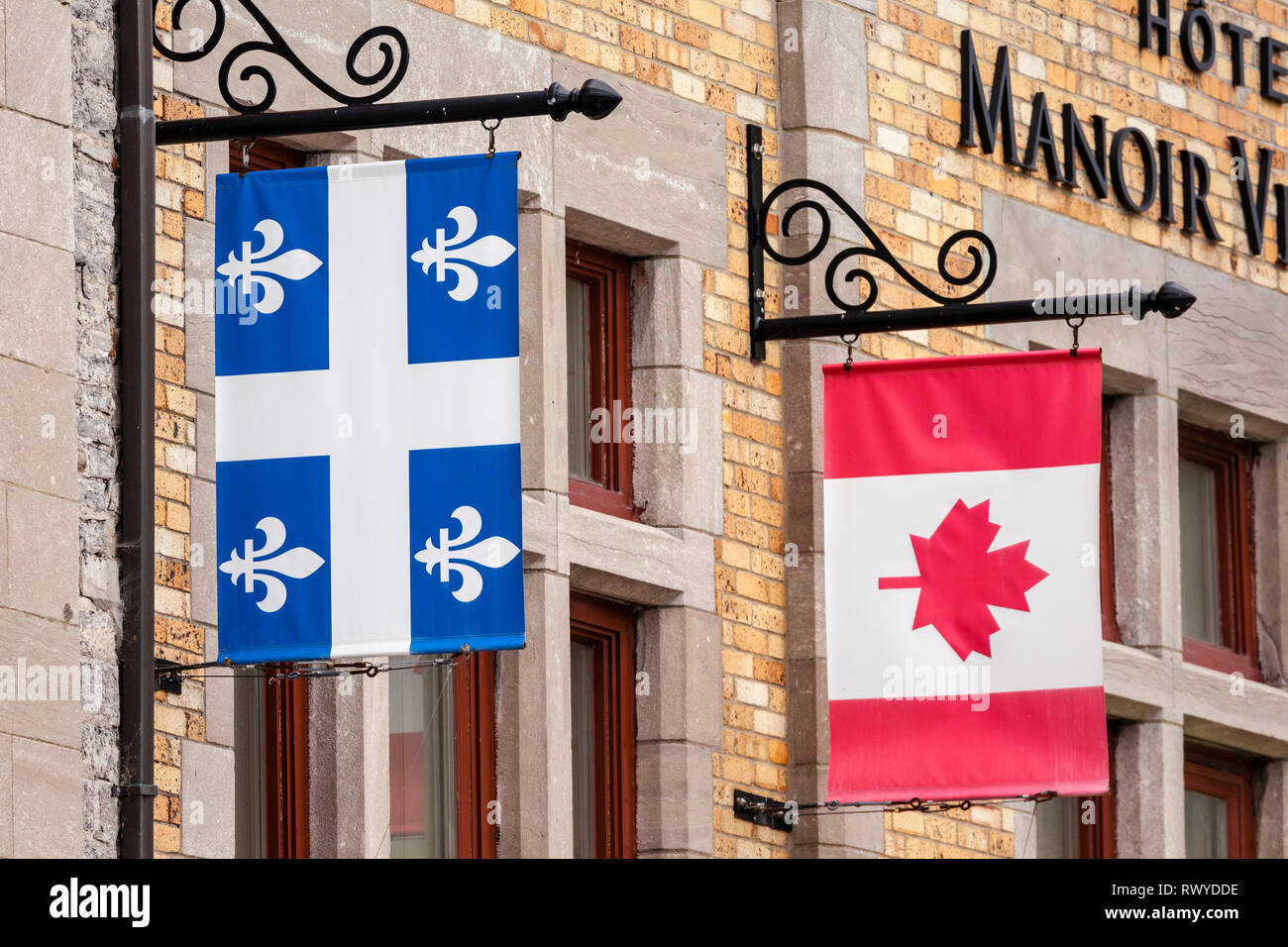 Flag banners hanging from vintage sign brackets on a brick building in Quebec, Canada - Stock Image