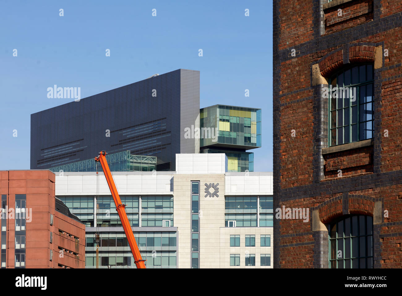 Manchester Civil Justice Centre peering over the roof of  Spinningfields Manchester - Stock Image