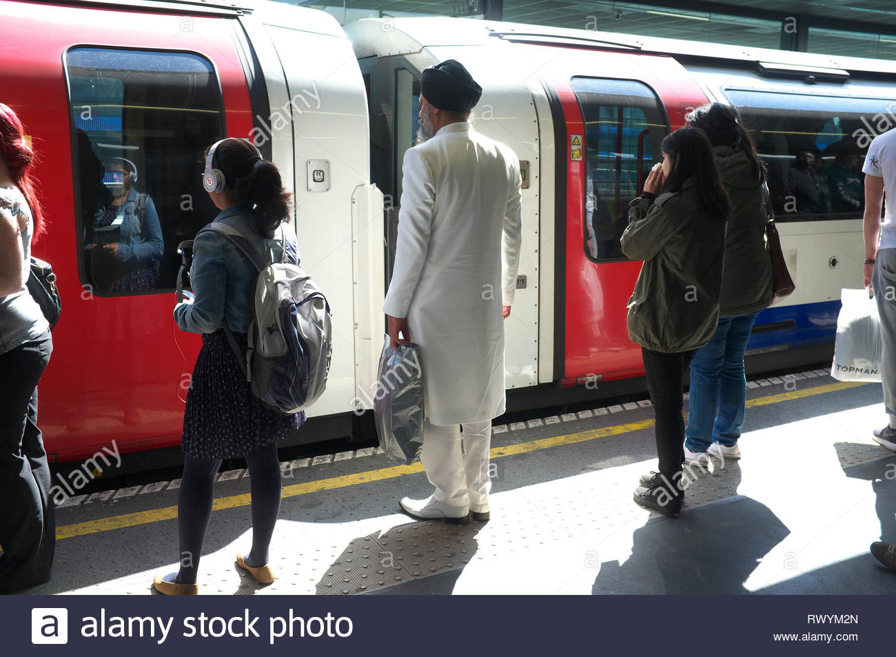 A smart dressed Indian man wearing a white suit and shoes awaits his train. London Underground, UK. Stock Photo