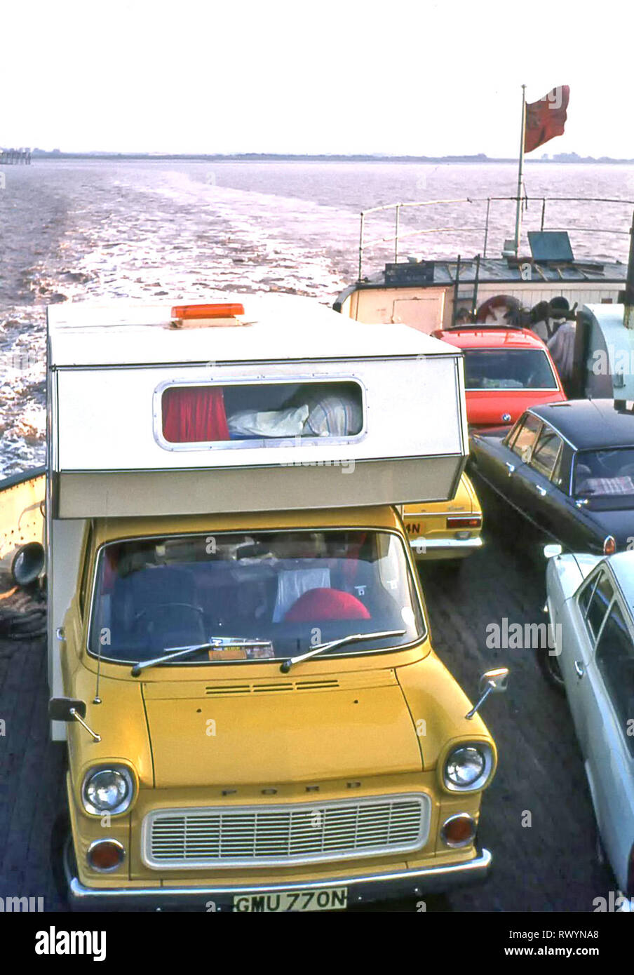 Purpose made RV camper van motorhome built 1970s on yellow Ford Transit chassis loaded on Scottish Highlands car ferry family touring holiday 1974 UK - Stock Image