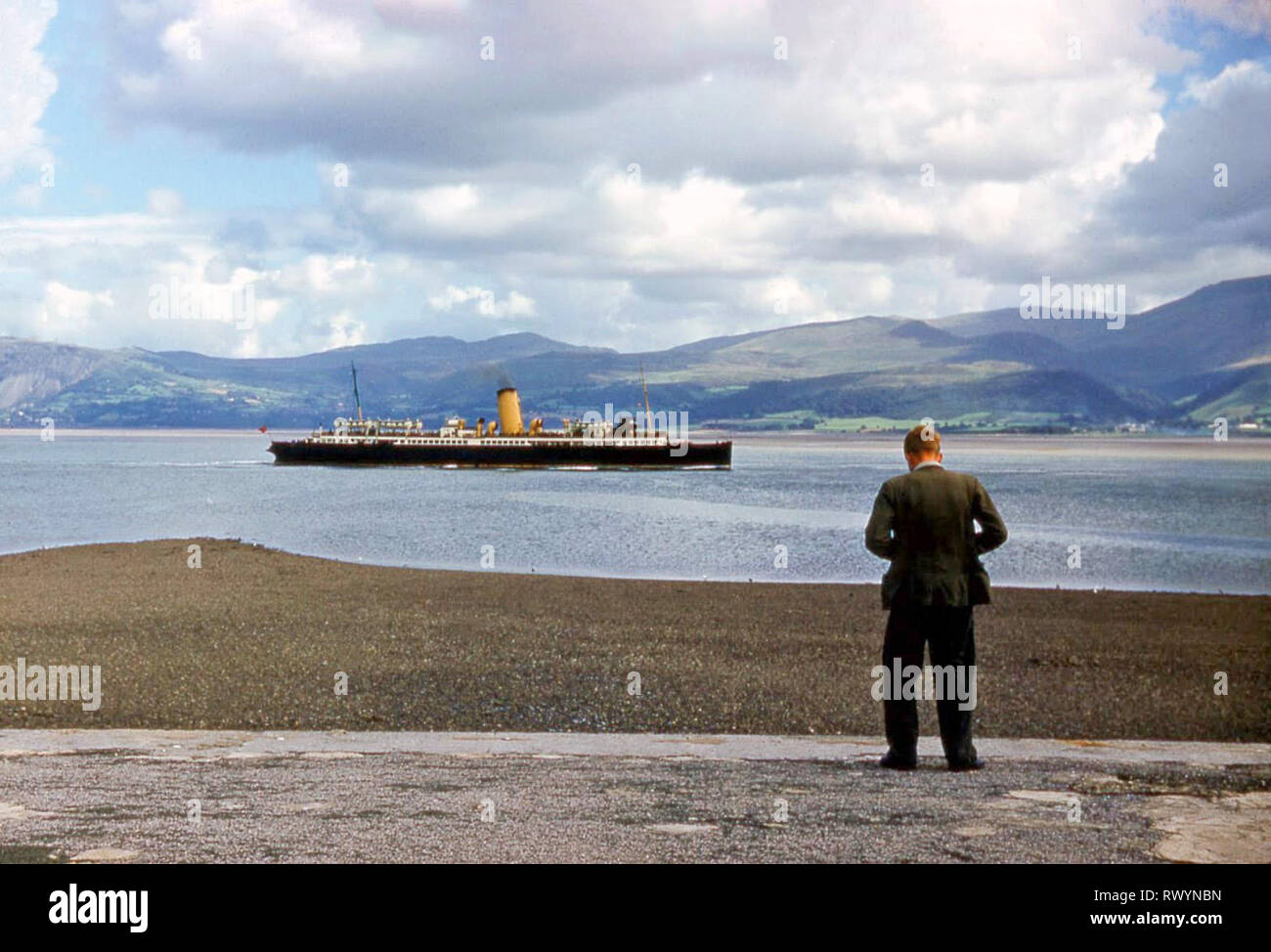 Young man taking photos waist level camera historical 1960s 60s archival view passenger ship St Tudno in Menai Straits landscape passing Beaumaris UK Stock Photo