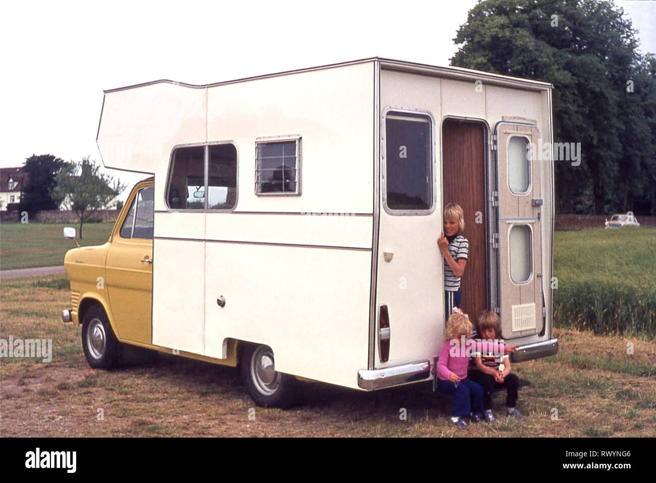Purpose made RV camper van motorhome built 1970s on yellow Ford Transit chasis 3 young childen 70s family holiday trip around East Anglia England UK - Stock Image