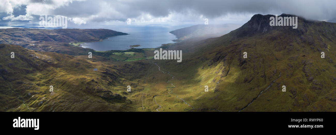 An aerial panorama looking down Gleann a Chaiginn Mhoir towards Loch Buie showing Ben Buie and an extensive view along the west coast. - Stock Image