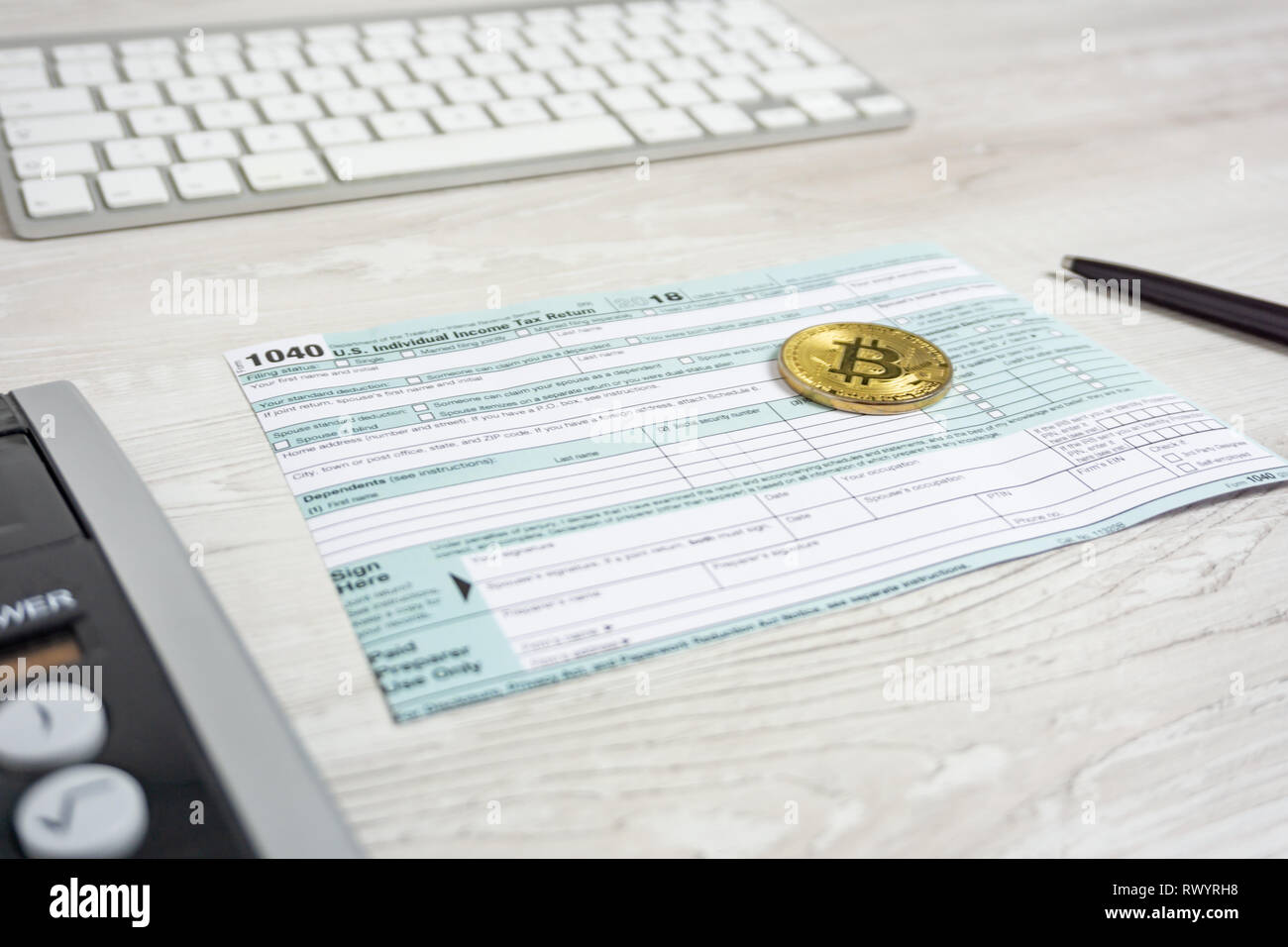 The pen, bitcoins and calculator on the tax form 1040 U S