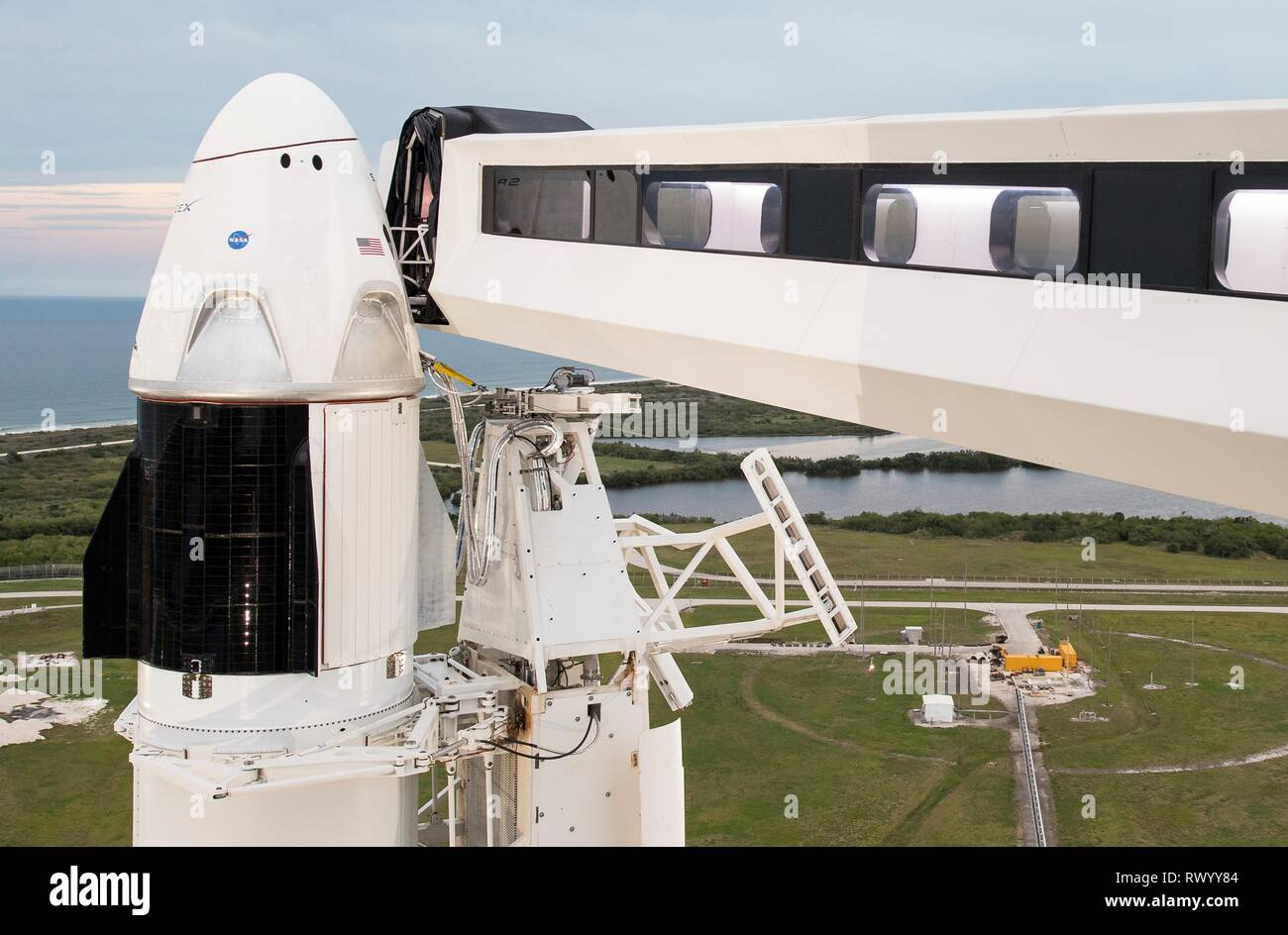 The SpaceX Crew Dragon spacecraft atop the Falcon 9 rocket and crew access way on the launch pad of Launch Complex 39A ready the launch of the Demo-1 mission at the Kennedy Space Center March 1, 2019 in Cape Canaveral, Florida. - Stock Image