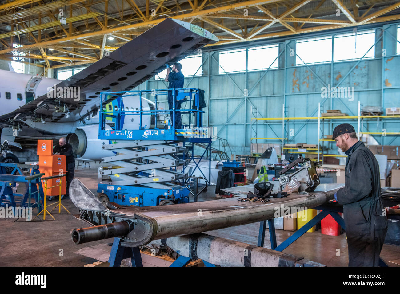Disassembly of passenger aircraft by E-cube solutions at St Athan's airbase south Wales. Various parts of the aircraft are sold on, re purposed etc. Or whole aircraft can be bought and stripped down or 'teared down' as it's known, according to the customer requirements.The engine's are often the most valuable parts of the aircraft and can be worth as much as 2 - 3 million GBP. This being so many carriers only lease the engines and the owners then decide on their fate once the aircraft has been retired from service. Other parts might be sold off and repurposed as furniture for the home, office - Stock Image