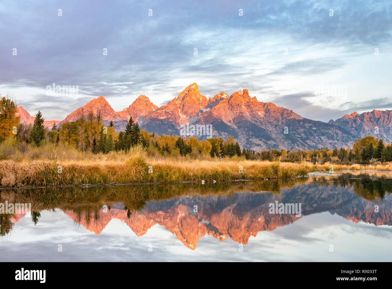 Mountains glow red at sunrise, Grand Teton Range mountain range reflected in the river, autumn landscape on Snake River - Stock Image