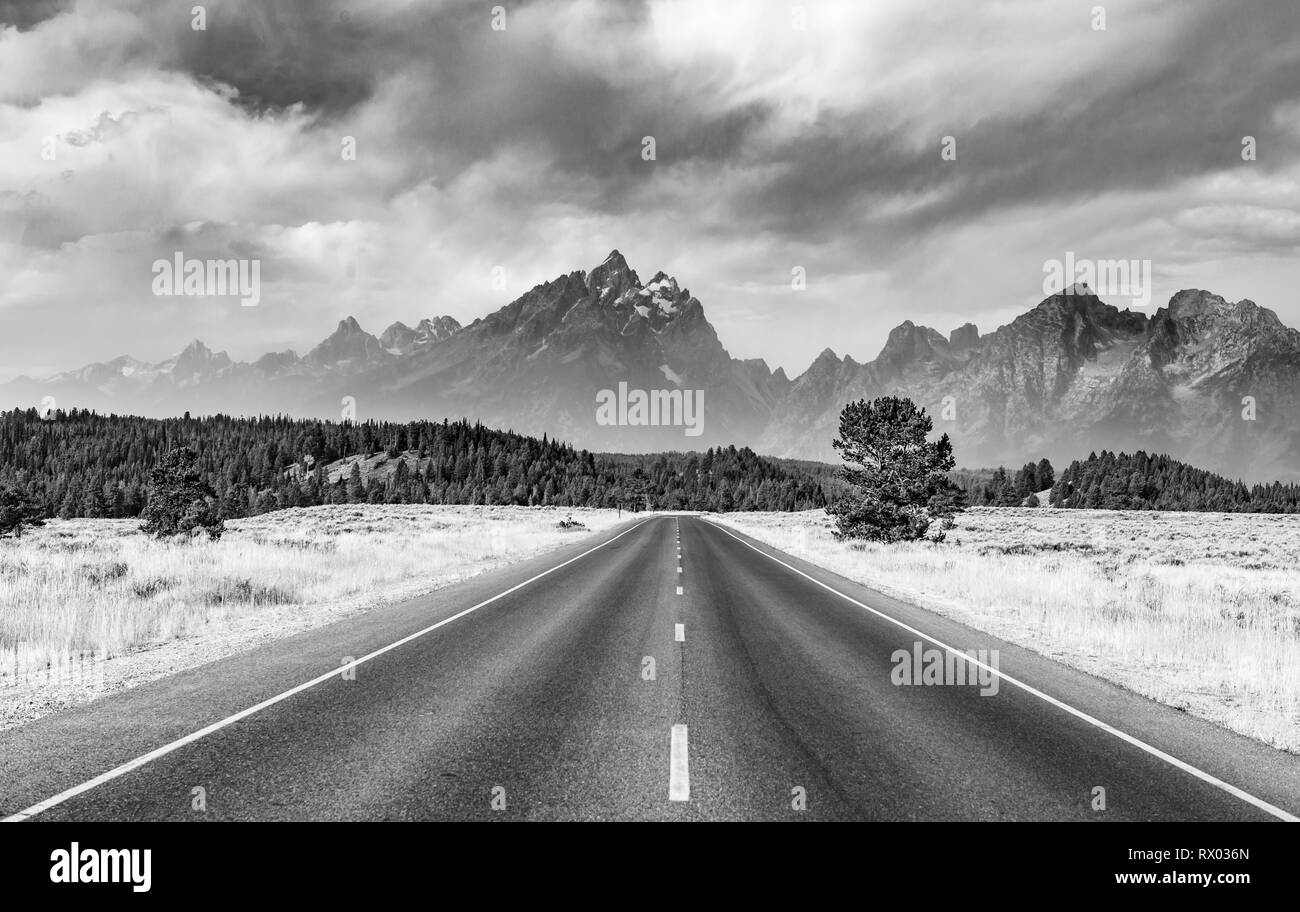 Black and white, country road in front of rugged mountains with cloudy skies, Grand Teton Range, Grand Teton National Park - Stock Image