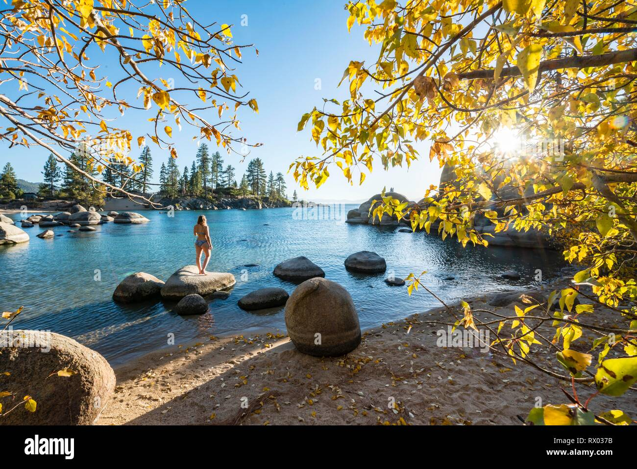 Young woman in bikini standing on a round stone in the water, bay at lake Lake Tahoe, Sand Harbor State Park, shore, California Stock Photo
