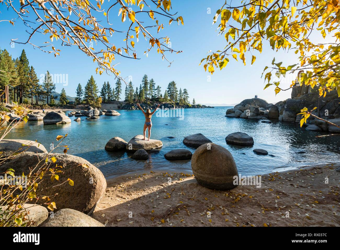 Young woman in bikini standing on a round stone in the water, bay at lake Lake Tahoe, Sand Harbor State Park, shore, California - Stock Image