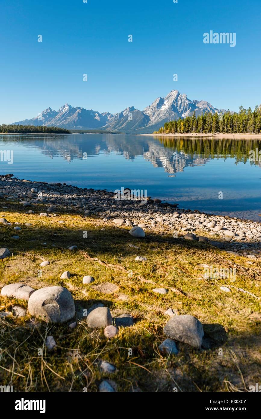 Mountains reflected in a lake, Colter Bay Bay, Jackson Lake, Teton Range Mountain Range, Grand Teton National Park, Wyoming, USA Stock Photo