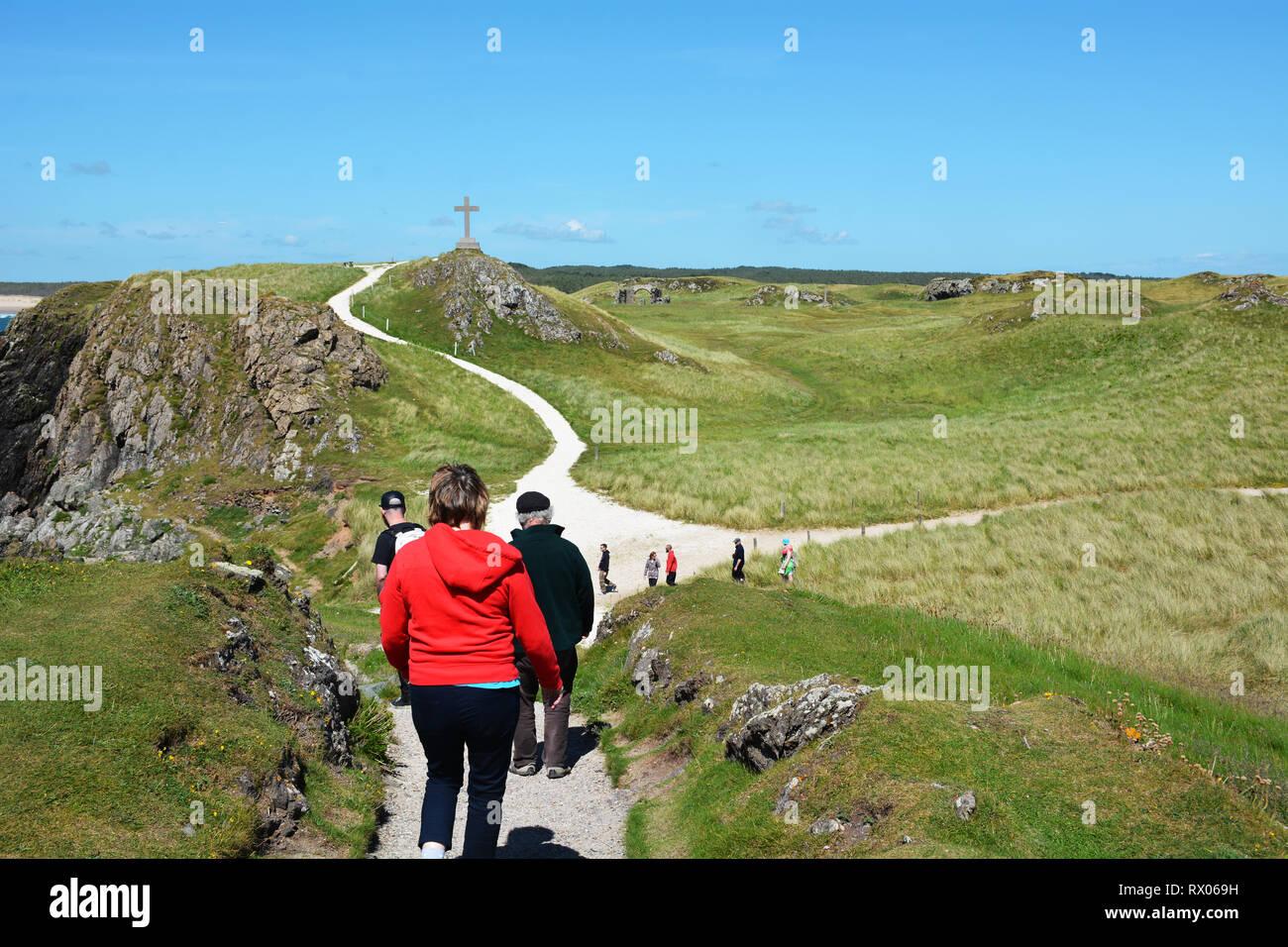 Walking towards the cross from the lighthouse on Llanddwyn Island Stock Photo